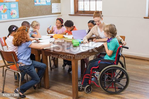 istock Pretty teacher helping pupils in classroom 472977300