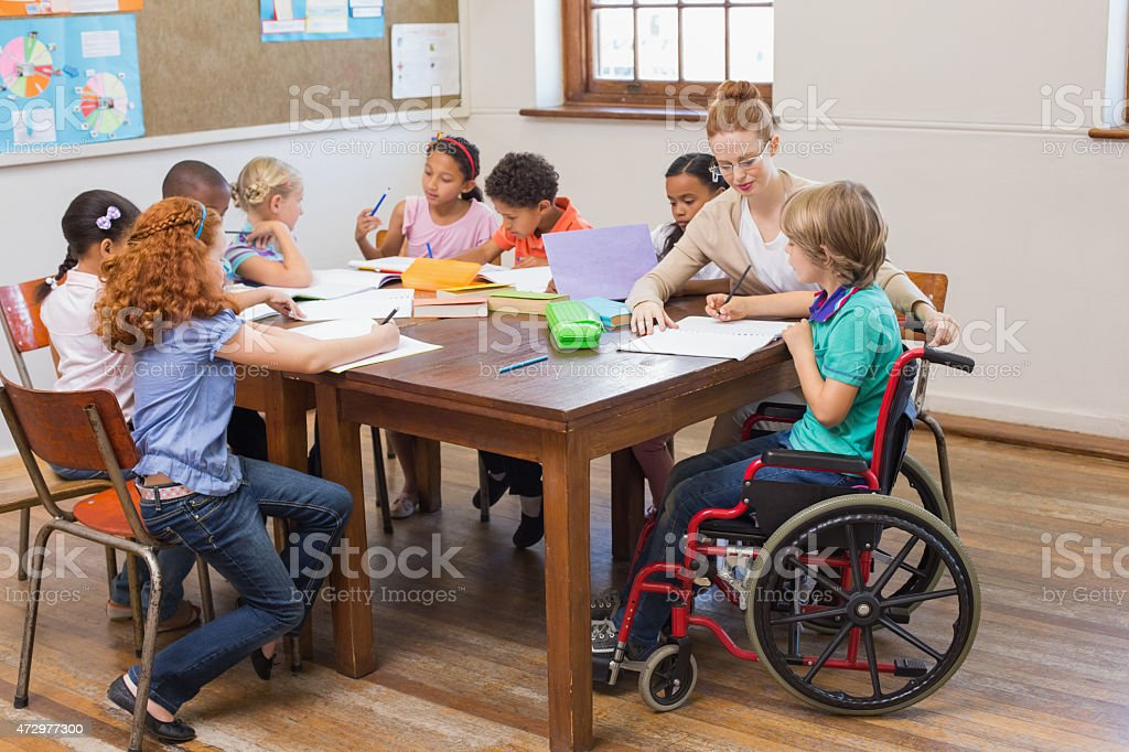 Pretty teacher helping pupils in classroom stock photo