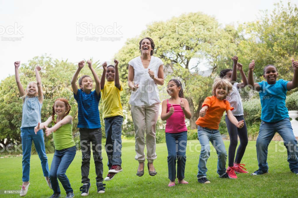 Pretty teacher jumping with pupils outside stock photo