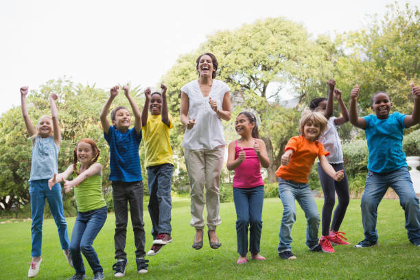 pretty teacher jumping with pupils outside - african youth jumping for joy stock photos and pictures