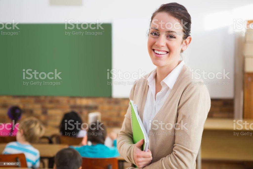 Professora bonita sorrindo para a câmera na parte traseira da sala de aula - foto de acervo