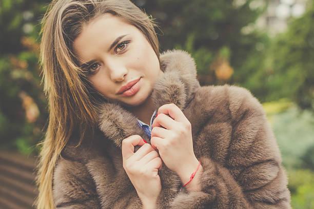 pretty teen girl is wearing fur coat - wintermantel damen wolle stock-fotos und bilder