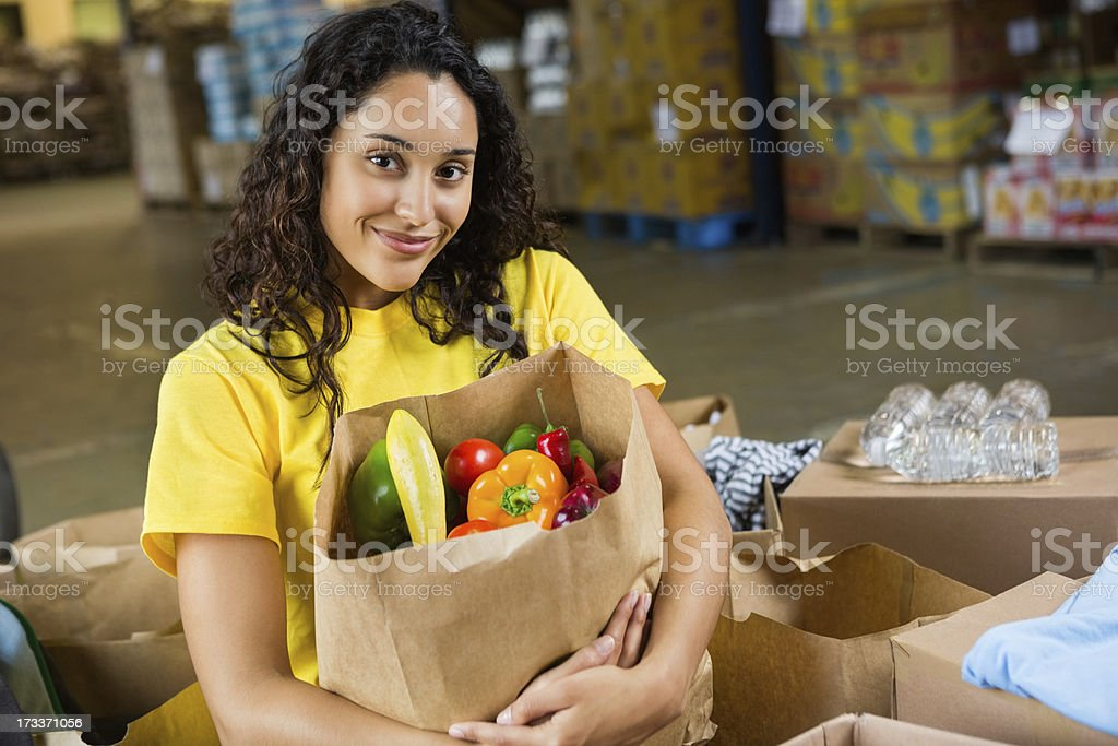 Pretty teen girl volunteer holding bag of healthy food donations royalty-free stock photo