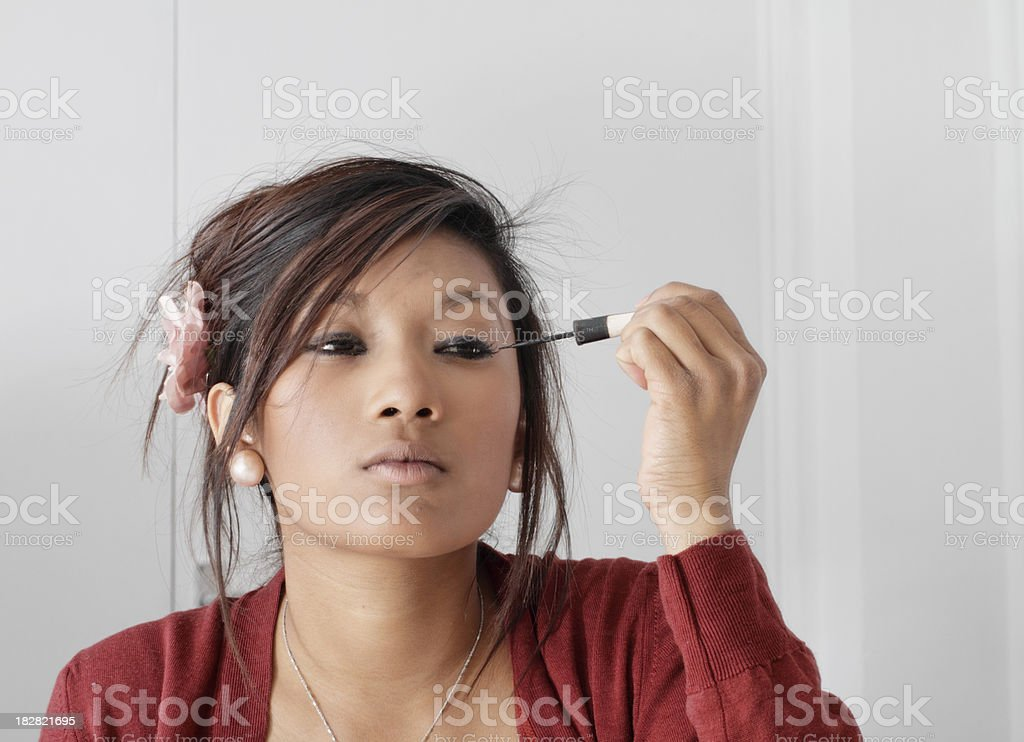 Pretty teenager Guyanese girl putting on eye make-up stock photo