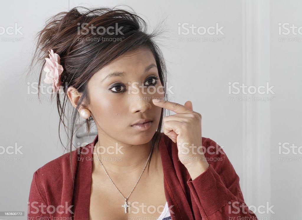 Big-eyed pretty teenager Guyanese girl putting on make-up stock photo