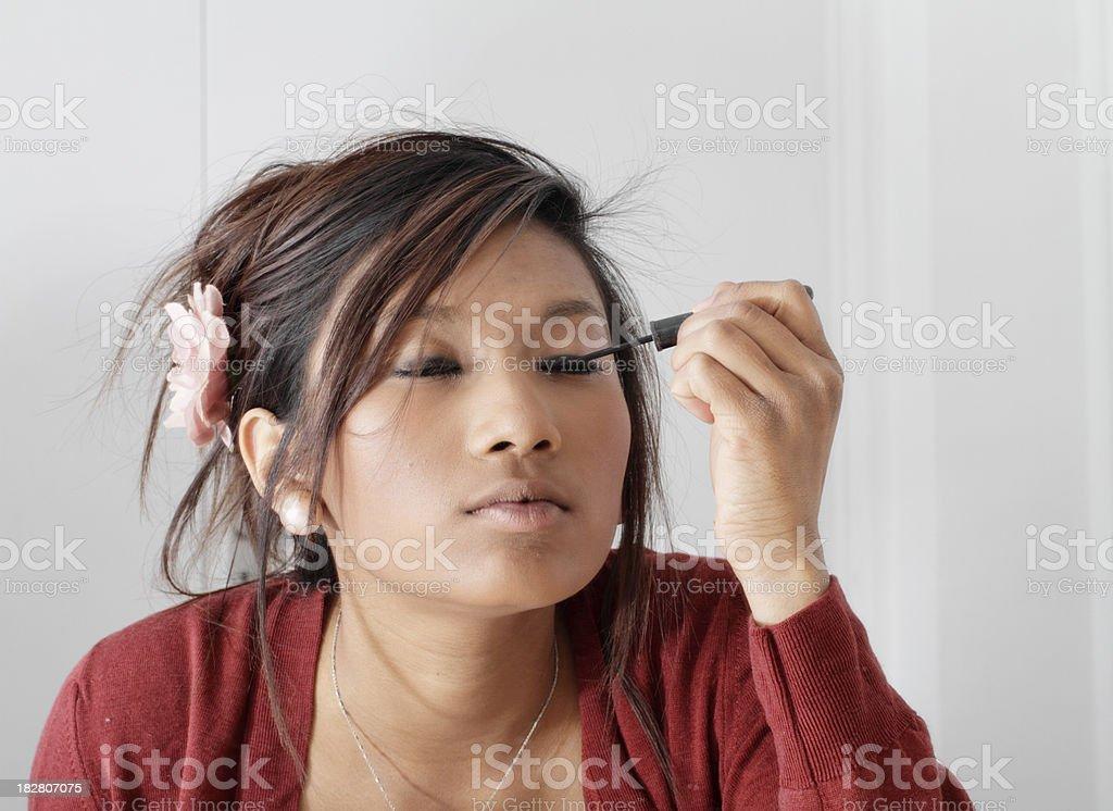 Pretty teenager Guyanese girl putting make-up on eyelashes stock photo