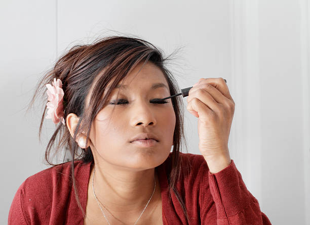 pretty teenager guyanese girl putting make-up on eyelashes - whiteway guyanese stock photos and pictures