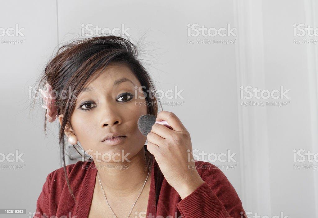 Pretty teenager Guyanese girl putting on blusher make-up stock photo