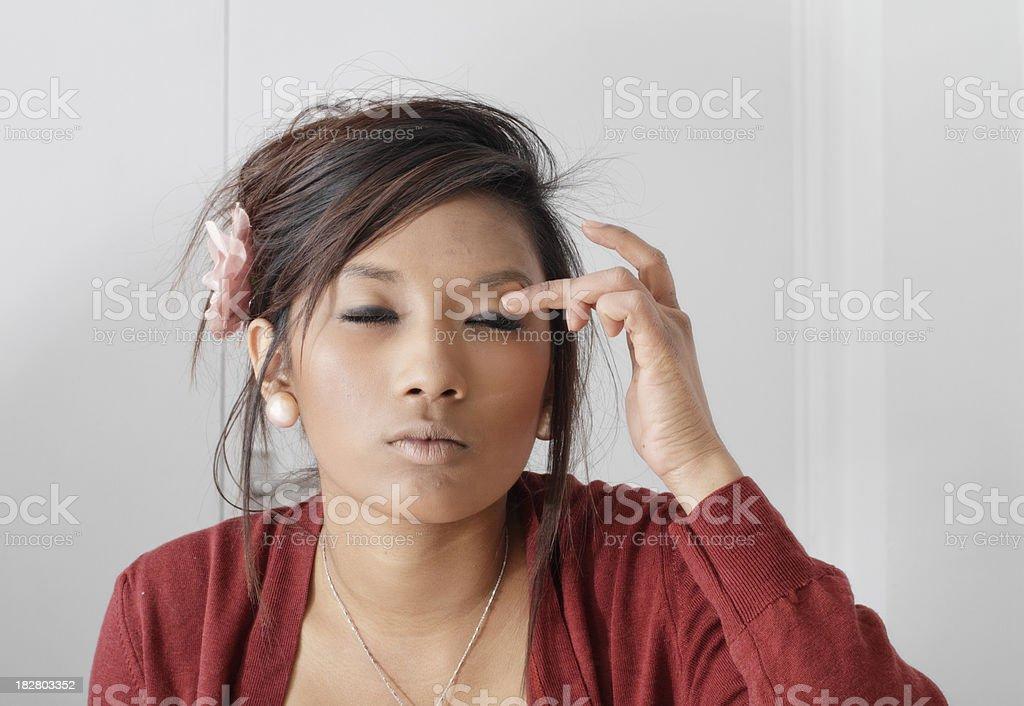 Pretty teenaged Guyanese girl squinitng putting on make-up stock photo