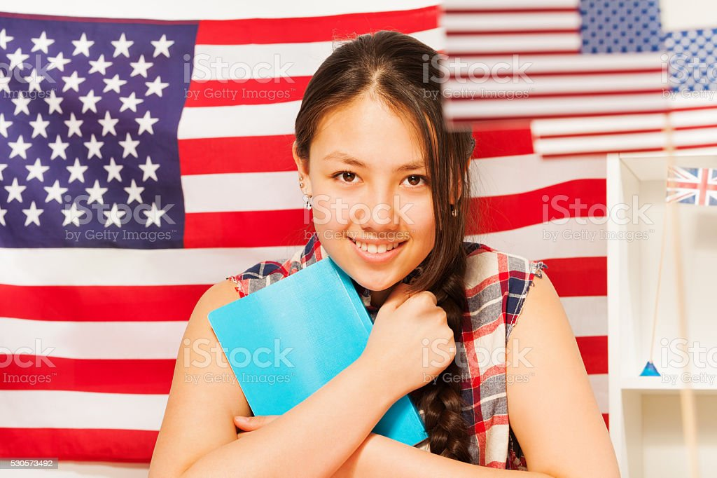 Pretty teenage girl with books studying English stock photo