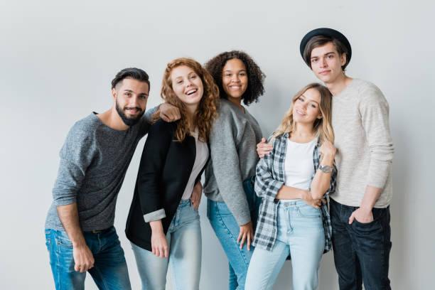 Chicas adolescentes bonitas y sus novios en ropa casual divirtiéndose - foto de stock
