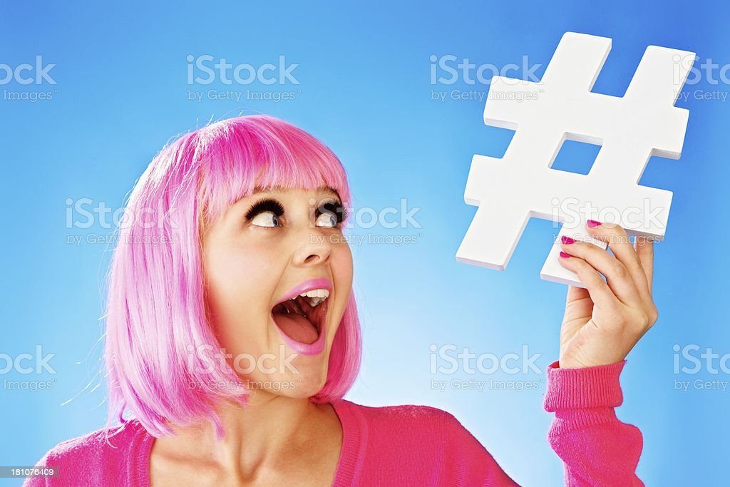 Pretty teenager in pink wig holds handmade hashtag sign, laughing stock photo