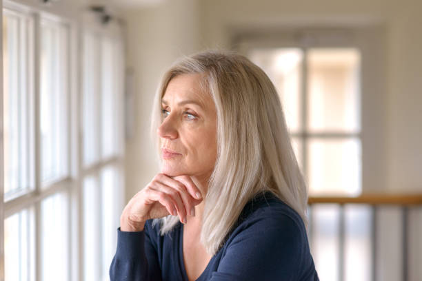 Pretty thoughtful woman with serious expression Attractive thoughtful woman with serious expression standing with her hand to her chin staring quietly out of a large window introspection stock pictures, royalty-free photos & images