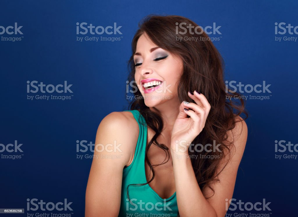 Pretty toothy laughing makeup woman with hand near hair on blue background. Closeup bright portrait stock photo