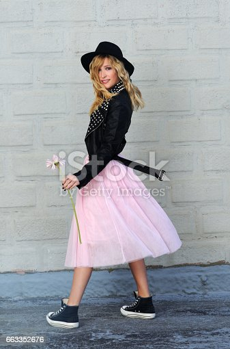 pretty trendy blond girl posing in black leather jacket and pink tulle skirt