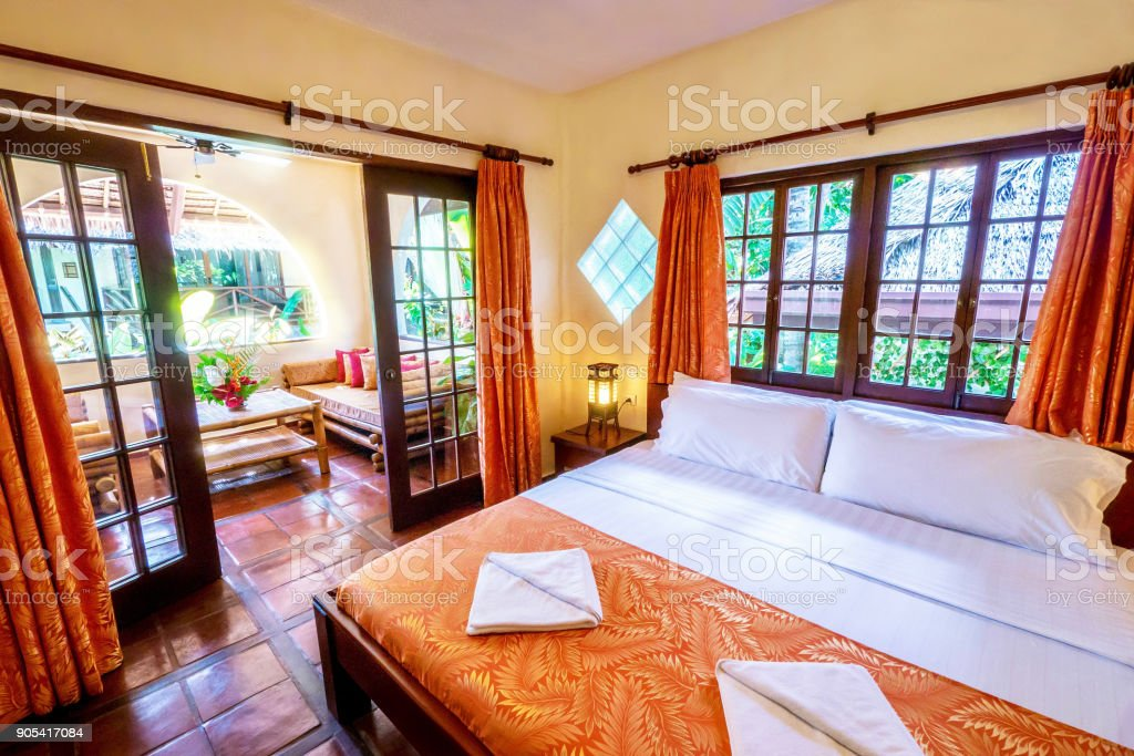 Pretty tropical resort bedroom with yellow walls and wooden french windows and doors opening onto a terra-cotta tiled balcony with rustic furniture, in a garden setting. stock photo