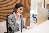 Pretty Vietnamese receptionist talking on telephone at her workplace