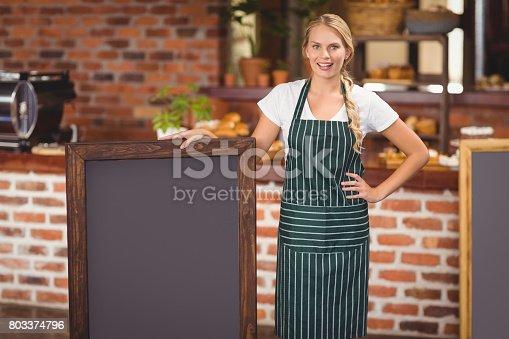 istock Pretty waitress holding a big chalkboard 803374796