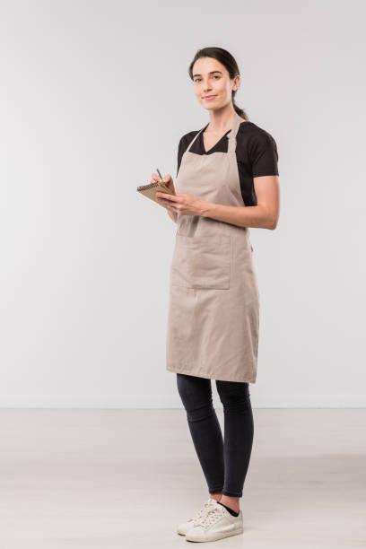 mooie serveerster in schort, zwarte skinny jeans en t-shirt maken van notities in kladblok - zwarte spijkerbroek stockfoto's en -beelden