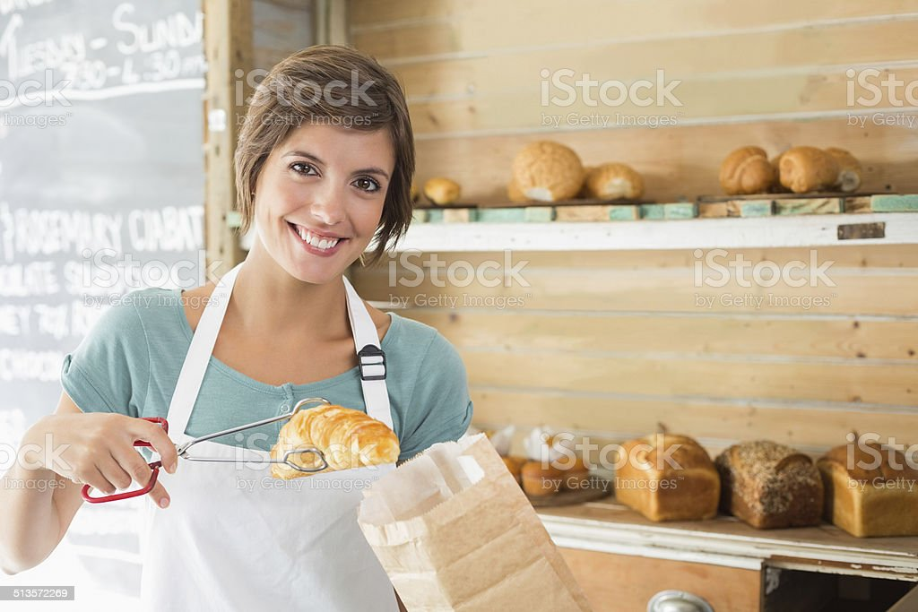 Pretty waitress picking up croissant stock photo