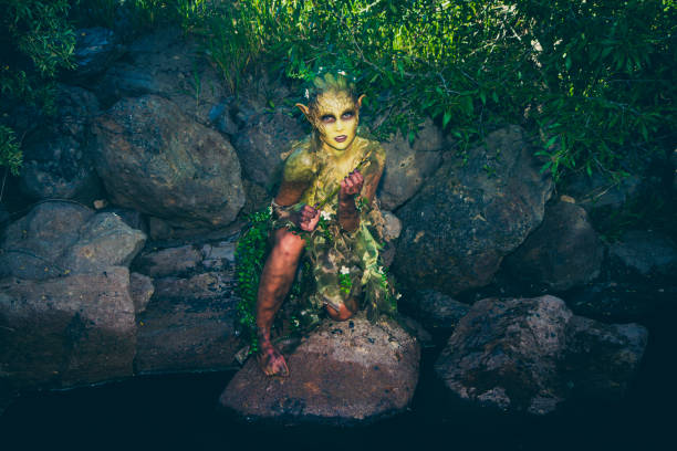 pretty water nymph fantasy creature near a creek - elfen fantasy stock-fotos und bilder