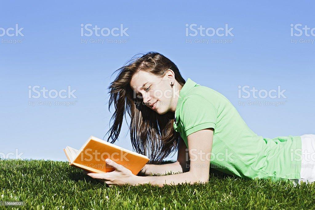 Pretty windblown brunette lies in field, reading royalty-free stock photo