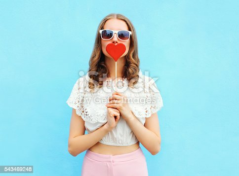 529664088istockphoto Pretty woman and lollipop over colorful blue background 543469248