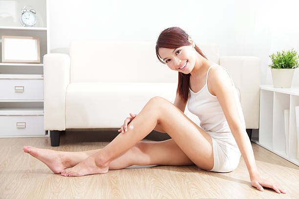 pretty woman applying cream on her attractive legs stock photo