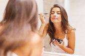 美しい女性はのアイシャドウ、鏡の前に