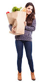 Cute young Hispanic woman carrying a big bag full of groceries against a white background