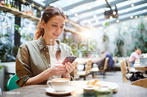 Smiling pretty young woman in casual shirt sitting at table in cafe and checking messenger while using smartphone