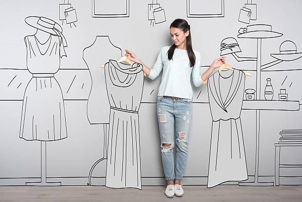 pretty woman choosing dresses in mall - damen jeans sale stock-fotos und bilder