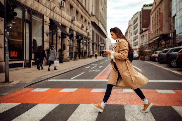 mooie vrouw die de straat kruist - street style stockfoto's en -beelden