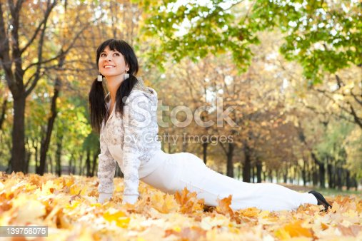 istock Pretty woman doing yoga exercises in the autumn park 139756075