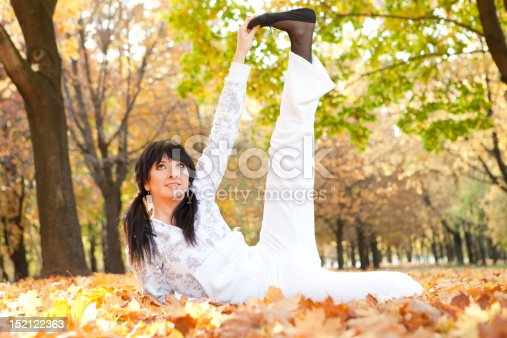 istock Pretty woman doing yoga exercises in the autumn park 152122363