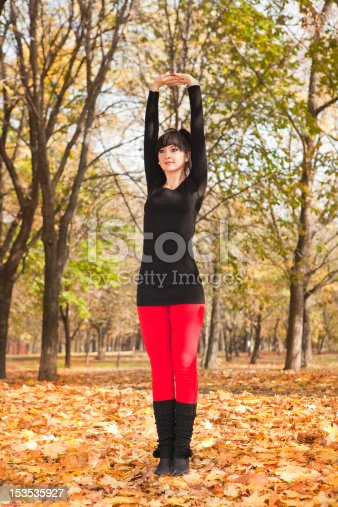 istock Pretty woman doing yoga exercises in the autumn park 153535927
