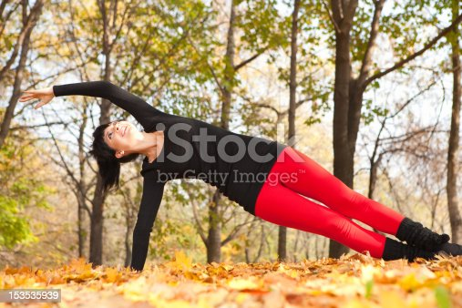 istock Pretty woman doing yoga exercises in the autumn park 153535939