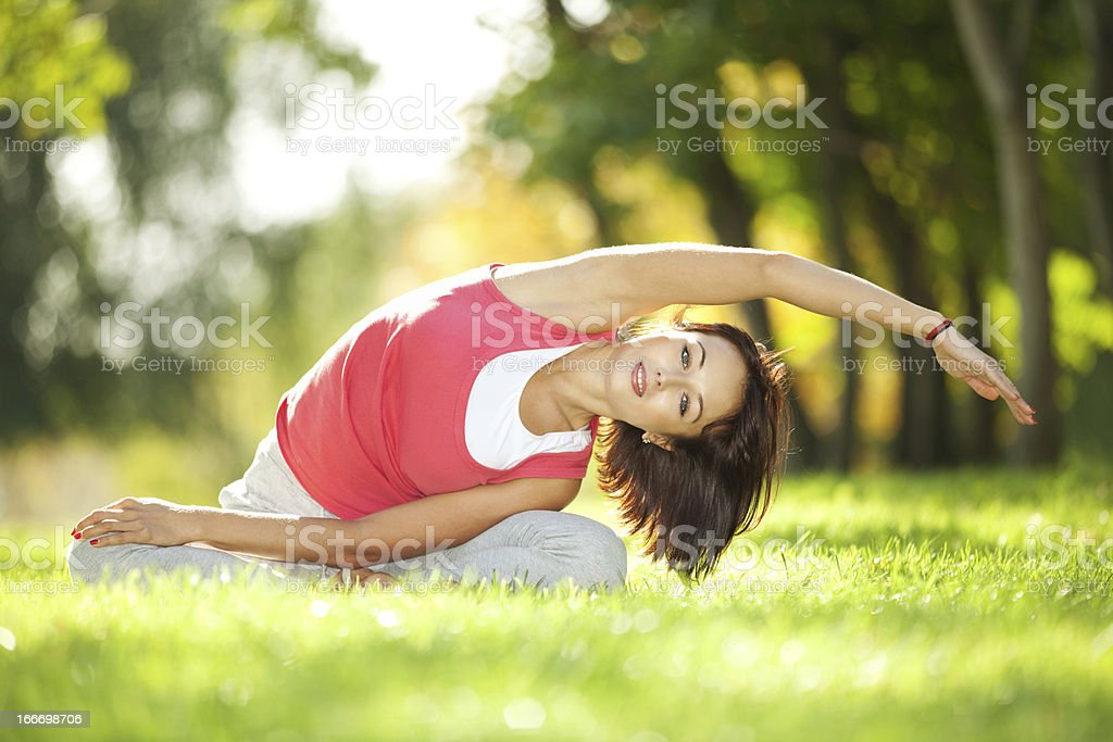 Pretty woman doing yoga exercises in the park royalty-free stock photo