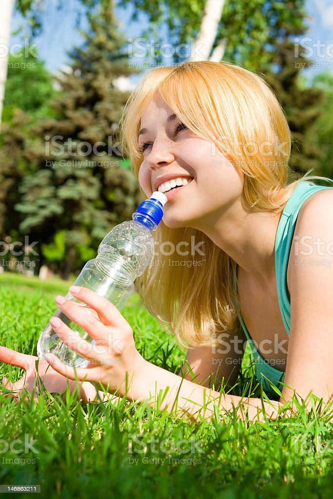pretty woman drinking water on the summer glade royalty-free stock photo