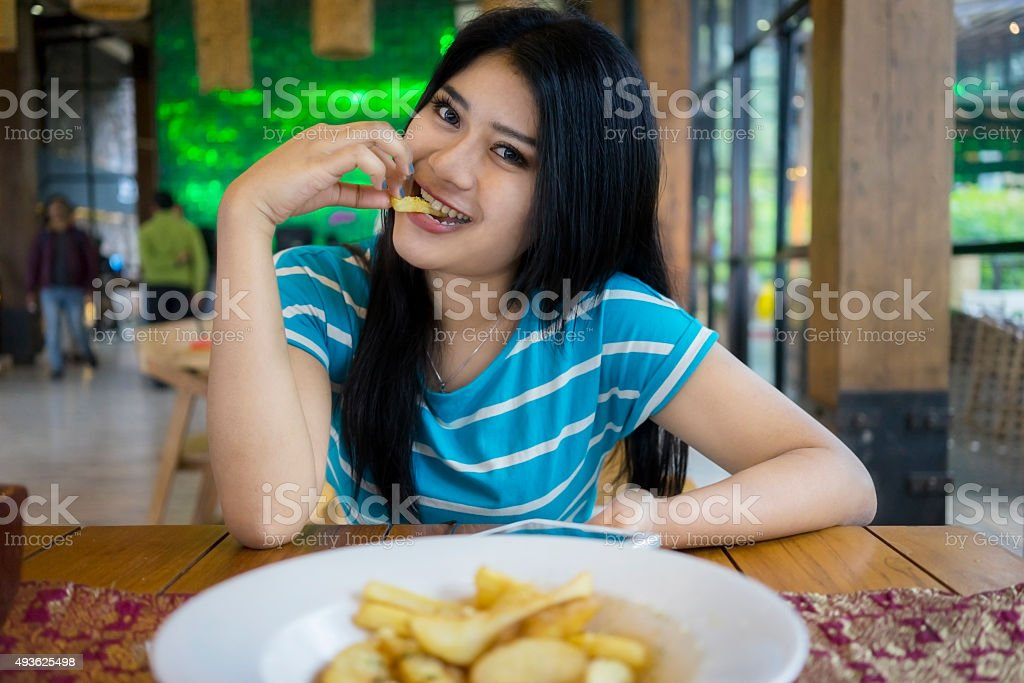 Pretty woman eating french fries at cafe stock photo