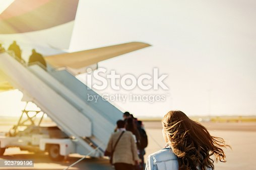 469824732istockphoto Pretty woman getting in to plane 923799196