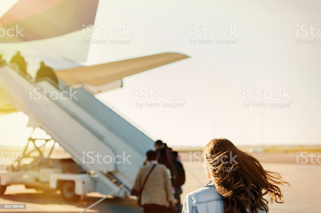 Pretty woman getting in to plane stock photo
