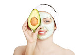 Beautiful woman with clay facial mask and avocado. isolated on white