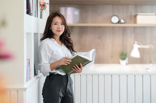 istock Pretty woman holding book and standing in office. 1176252245