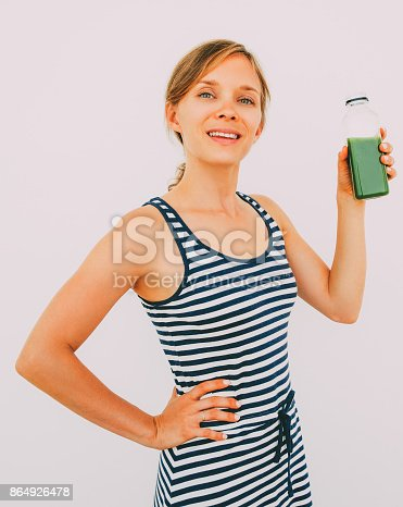 Closeup of smiling young attractive woman looking at camera and holding bottle of fresh green juice. Isolated view on grey background.