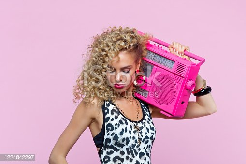 807419930 istock photo Pretty woman in 80's style outfit holding boom box 1224842297