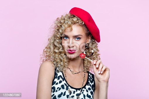 Fashion portrait of beautiful blond curly hair woman wearing leopard print top and red beret. Female in 80's style outfit holding lollipop, smirking at camera. Studio shot on pink background.