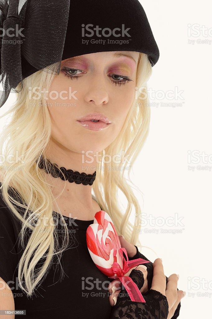 Pretty Woman In Black Hat & Chocker Holding Heart Sucker royalty-free stock photo
