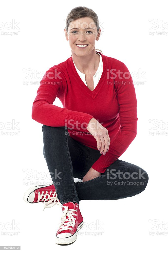 Pretty woman in casuals sitting on the floor stock photo