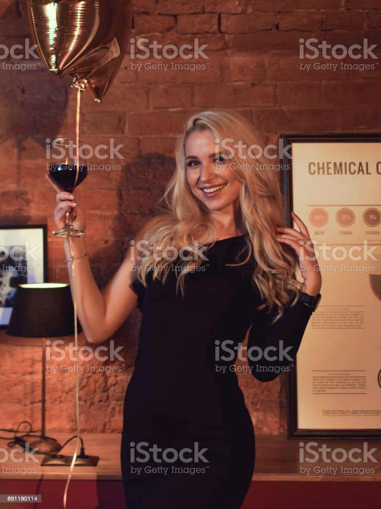 Pretty woman in cocktail dresses posing with balloons at birthday party in cafe stock photo